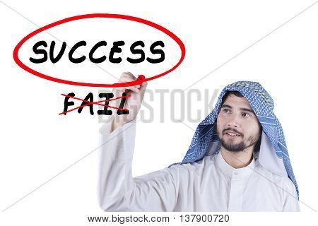 Portrait of Arabian young businessman choosing the success word on the whiteboard