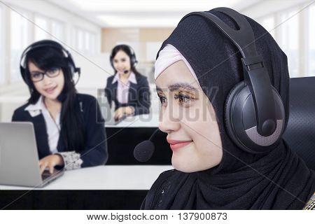 Portrait of beautiful Arabian helpline operator working in the office with her team