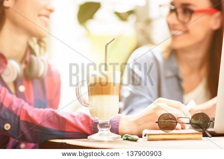 Flavored latte. Close up of creamy latte in coffee shop with young smiling girl talking in background