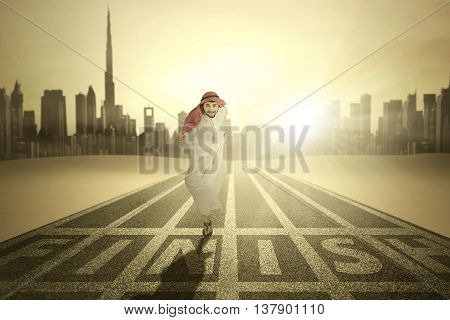 Portrait of Arabic young businessman running through the finish line on the road