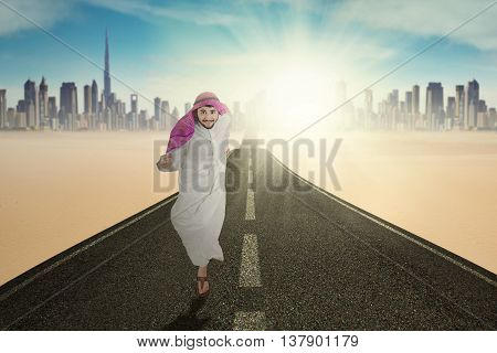 Photo of Arabic businessman running on the highway while wearing islamic clothes