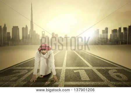 Picture of Arabic businessman ready to race and kneeling on the start line with numbers 2016