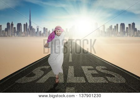 Arabic businessman running on the road with a text of Sales and wearing islamic clothes