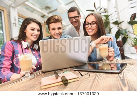 Enjoying time together. Close up of group of friends enjoying fun moments, using laptop at coffee shop