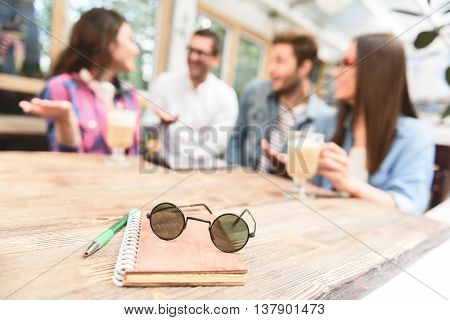 This is best place in town. Close up of sunglasses lying with notepad on wooden table in coffee shop with friendly comrades talking in background
