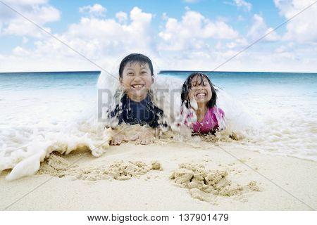 Two cheerful children enjoying holiday at the beach while lying on the sand and playing wave