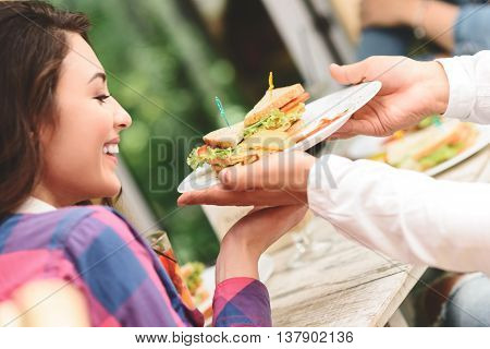 This looks delicious. Portrait of pretty young woman eating massive, delicious sandwich in cafe