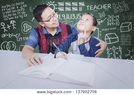 Portrait of a male teacher wearing glasses and teaches a little boy in the classroom with doodle on the chalkboard
