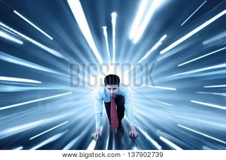 Young businessman ready to run on the road with fast motion blur background