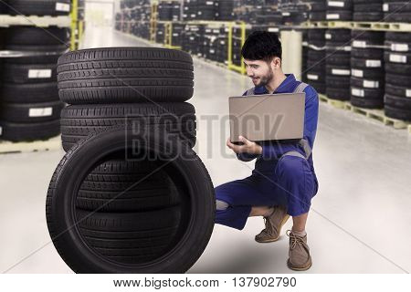 Portrait of Arabian mechanic checking the tires while holding laptop in the tire store