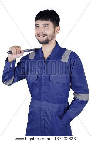 Arabian young mechanic holding a tool while wearing uniform in the studio isolated on white background