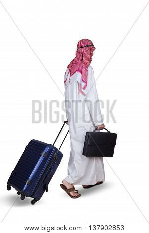 Middle eastern businessman walking in the studio while carrying suitcase and wearing islamic clothes