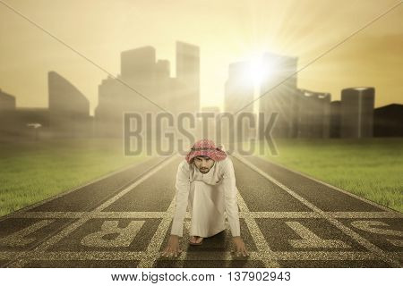 Portrait of muslim young businessman kneeling on the start line and ready to race on the road