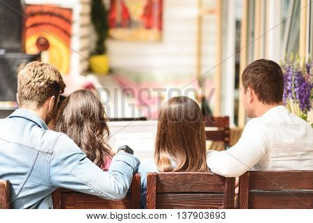 All together again. Back view of four friends sitting on wooden chairs in cafeteria and watching somewhere