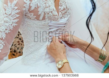 Morning Bride. Bridesmaid Helping The  Lacing Up Her Dress