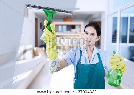 Portrait of young maid wearing uniform and apron cleaning the mirror with spray at the home