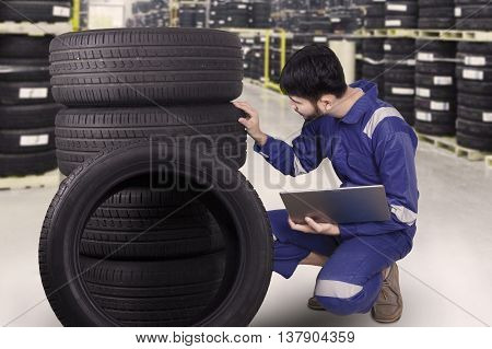Portrait of young technician working with laptop and check a stack of tires in the workshop