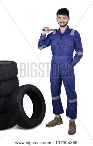 Arabian young mechanic standing in the studio while wearing uniform and holding a tool next to the tires