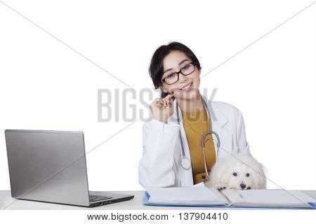 Young female veterinarian smiling at camera with maltese dog and laptop on desk isolated on white background
