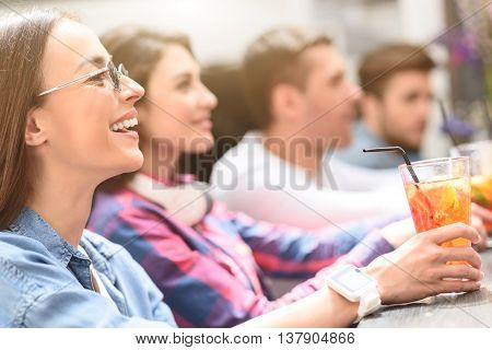 Spending quality time with my friends. Smiling girl in sunglasses sitting with friends in row, drinking cocktail and wearing smartwatch