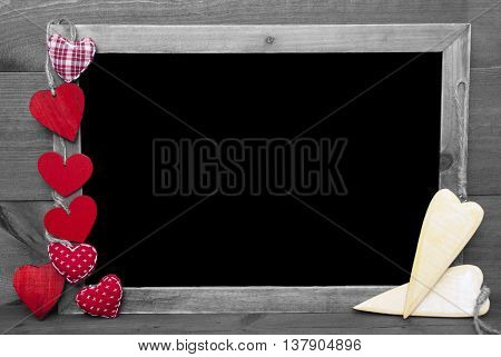 Chalkboard With Copy Space For Advertisement. Many Red Hearts. Wooden Background With Vintage, Rustic Or Retro Style. Black And White Image With Colored Hot Spots.