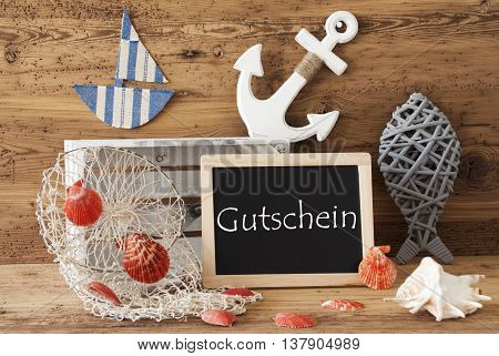 Blackboard With Nautical Summer Decoration And Wooden Background. German Text Gutschein Means Voucher. Fish, Anchor, Shells And Fishnet For Maritime Contex.