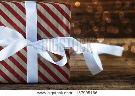 Macro Of Christmas Gift Or Present On Wooden Background. Copy Space For Advertisement. White Ribbon With Bow And Atmospheric Bokeh Effect