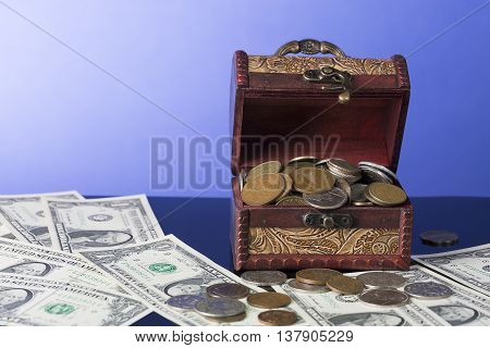 American dollar bills with chest filled with coins on blue background.