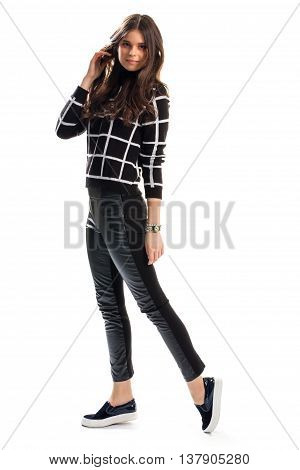 Girl in black checkered pullover. Skinny fit pants and shoes. Cute model wears autumn clothes. Leather and cotton.