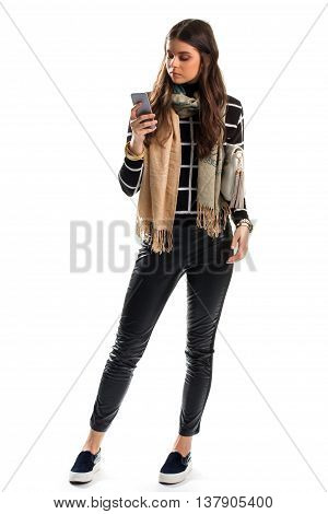 Woman in sweater holds phone. Scarf and black slip ons. Fashion model with new gadget. High speed of internet connection.
