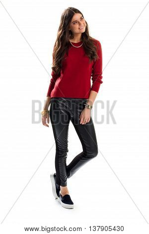 Girl in red sweater smiling. Skinny pants of black color. Attractive casual outfit. Professional model on white background.
