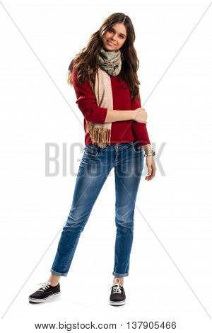 Girl in red sweatshirt smiling. Beige scarf and blue jeans. Stylish scarf with fringe. Brand new canvas shoes.