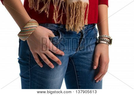Girl's hands on blue jeans. Denim pants and small watch. Wicker bracelet with colorful pattern. Everyday accessories from catalog.