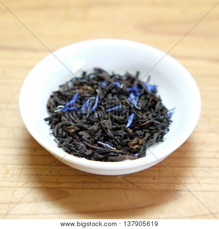 Dried loose leaf tea - Earl Grey cream, black tea leaves with blue cornflower petals. In a white dish on a rustic wooden background. Very shallow depth of field.