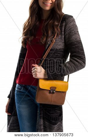 Young woman in sweater coat. Brown and yellow bicolor purse. Warm outerwear and simple jeans. Casual autumn style.