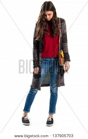 Lady in long sweater coat. Jeans and handbag with strap. Woolen outerwear and canvas shoes. Casual outfit from lookbook.
