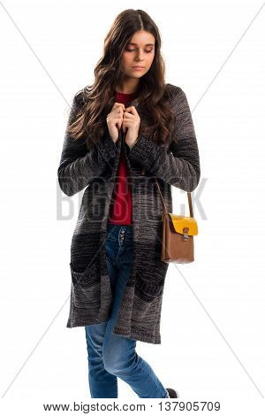 Woman in long outerwear. Striped sweater coat and jeans. When it's cold outside. Feeling of loneliness.