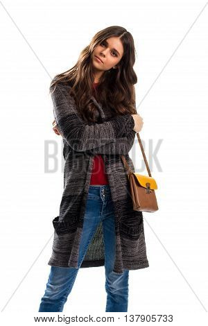 Young woman in striped outerwear. Two-tone bag with strap. Blue slim fit jeans. Sweater coat of natural wool.