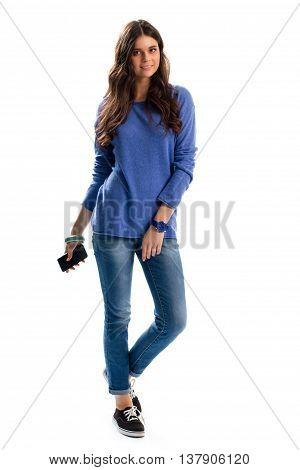 Lady in blue pullover. Young woman holds phone. Sports watch of blue color. Spring outfit with fabric shoes.