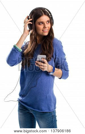 Smiling woman in headphones. Lady in sweater with phone. Gadget with lots of functions. Best wired headphones.