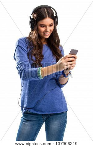 Smiling woman with headphones. Lady looks on cell phone. Tons of new impressions. New durable headphones.
