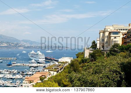 Monte Carlo harbor with the ancient Prince's Palace of Monaco, luxury yachts in the water, and the city skyline