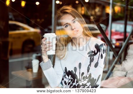 Beautiful caucasian woman sitting in city coffee shop near the window drinking coffee from paper cup and looking at the camera