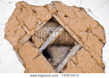 Close view of an old house wall - fragment of the old building technology. Logs laths clay with straws parget and slaked lime