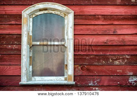 Old widow frame with dirty glass on red wooden house wall