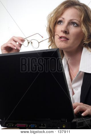 Business Woman Daydreaming While Working On Laptop