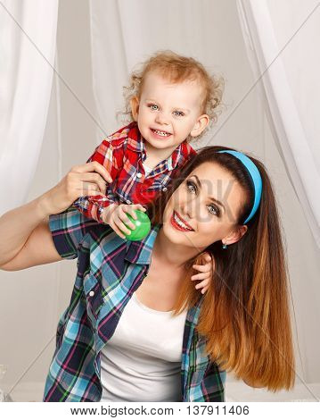 Mother and daughter at home. Young mother and baby daughter hugging and playing ball. Girls dressed in plaid shirt. Mother carry piggyback daughter. Family time
