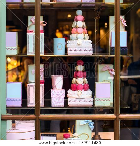 Beautiful colourful tasty macaroons cakes sweets and presents in the boxes display in window at the street shop