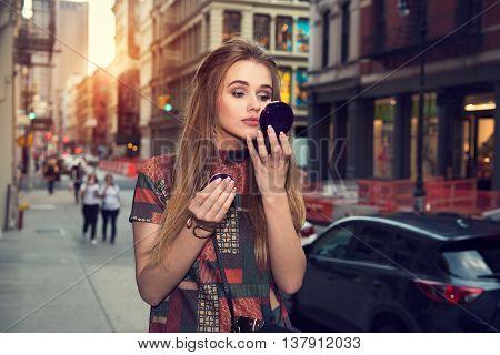 Beautiful girl doing makeup and walking on city street
