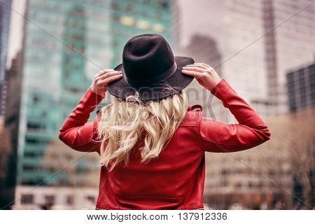 A young woman wearing a hat is walking in the streets of New York City